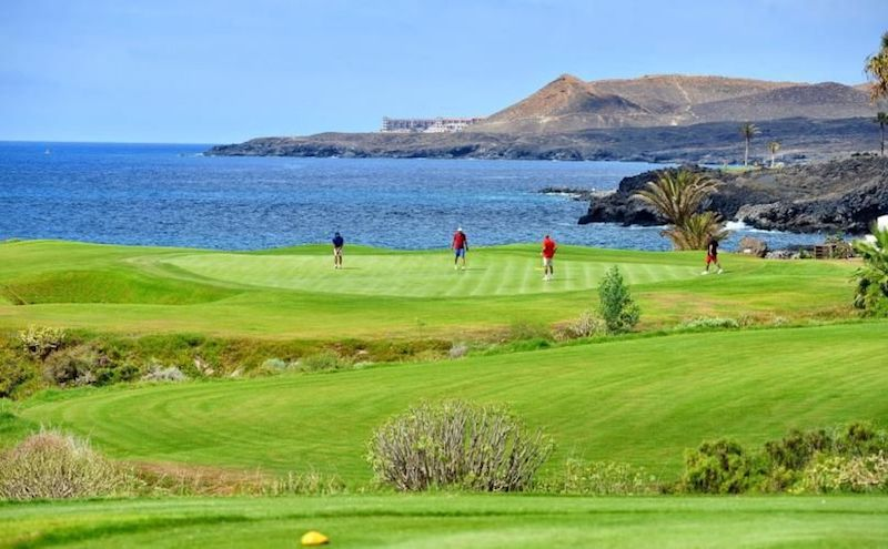 Golfers on the green on an oceanside hole on Tenerife's Amarilla Golf